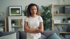 Портрет расстроенной и обиденной Афро-американской дамы стоя дома с пересеченными оружиями делающ сердитую сторону хмурясь и акции видеоматериалы