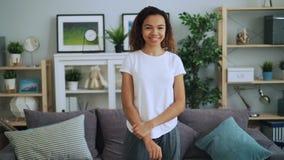 Портрет очаровывать Афро-американскую девушку в случайной одежде стоя в стильной современной квартире, усмехаться и смотреть видеоматериал