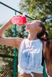 Портрет sporty молодой сексуальной женщины выпивая крутую воду от бутылки на спортивной площадке лета outdoors стоковые фотографии rf