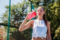 Портрет sporty молодой сексуальной женщины выпивая крутую воду от бутылки на спортивной площадке лета outdoors стоковое фото rf