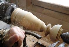 Ðœan rectifie un chandelier en bois sur un tour photos libres de droits