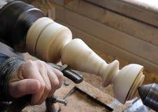 Ðœan rectifie un chandelier en bois sur un tour photographie stock