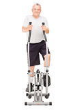 Мature man excersing on a cross trainer Stock Images