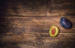 Оne enige pruim en de helft van pruim met steen over donkere houten raad De achtergrond van het fruit Tekstruimte Hoogste mening royalty-vrije stock fotografie