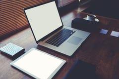Оpen便携式计算机和数字式片剂有白色空白的拷贝的间隔屏幕对于文本信息或内容 免版税图库摄影