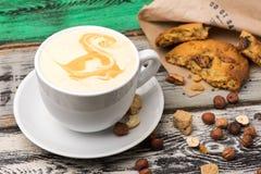 Ð在一个白色杯子的¡ appuccino用曲奇饼和榛子 库存照片