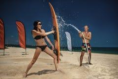 Ð获得¡的ouple与飞溅夏天雨的水管的乐趣 免版税库存图片