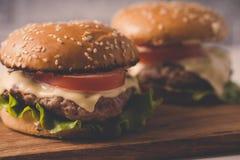 Ð  amburger of sandwich op pakpapier Heerlijke sandwichhamburger met vlees, kaas en verse groente stock fotografie