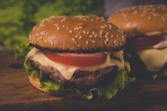 Ð  amburger of sandwich op pakpapier Heerlijke sandwichhamburger met vlees, kaas en verse groente royalty-vrije stock foto