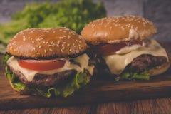Ð  amburger of sandwich op pakpapier Heerlijke sandwichhamburger met vlees, kaas en verse groente royalty-vrije stock fotografie