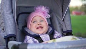 Ð ¡犹特人小女孩在婴儿车和smilingб坐街道,自然 影视素材