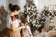Ð-¡ aring Mutter flicht die Borte ihrer kleinen Tochter, während zweite Tochter einen Baum des neuen Jahres im gemütlichen Li lizenzfreie stockfotografie