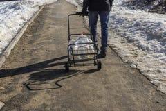 Ð-¡ ity Bewohner geht für klares Wasser mit leeren Wasserflaschen auf seinem Transportwagen stockfotos