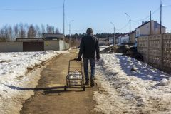 Ð-¡ ity Bewohner mit leeren Wasserflaschen auf seinem Transportwagen geht für klares Wasser stockbilder