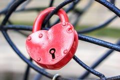 Ð-¡ losed det röda låset i form av hängningar för en hjärta på en järnstructu fotografering för bildbyråer