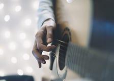 Ð ¡ loseup ενός ατόμου που παίζει την κιθάρα σε μια σπιτική ατμόσφαιρα, καθμένος σε μια καρέκλα σε ένα κλίμα του φωτός bokeh οριζ στοκ εικόνα με δικαίωμα ελεύθερης χρήσης