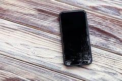 Ð ¡ loseup czerni smartphone z łamanym parawanowym szklanym lying on the beach na drewnianym stole Pojęcie zrzutu telefon, łamają zdjęcia stock