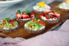 Ð ¡ loseup makro- set różne północne modne zakąski na smorrebrod żyta chlebie z czerwonym kawiorem i avocado, truskawki, zdjęcie royalty free