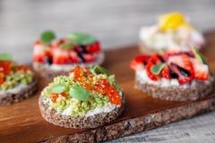 Ð ¡ loseup makro- set różne północne modne zakąski na smorrebrod żyta chlebie z czerwonym kawiorem i avocado, truskawki, obraz stock