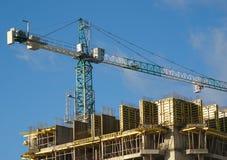 Ð ¡ onstruction, das Kran über Gebäudehaus hochzieht Lizenzfreies Stockbild