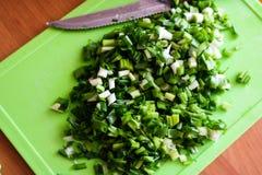 Ð ¡ podskakiwał zielone cebule na kuchni desce zdjęcie royalty free