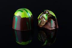 Ð ¡ sleepte met de hand gemaakt suikergoed met groene splachdecoratie en chocolade ganache en fruitgelei het vullen op zwarte ach royalty-vrije stock foto's