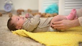 Дама массажируя ноги младенца, предохранение дисплазии соединений бедренной кости, уменьшая боль колики видеоматериал
