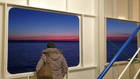 Дама смотря через уничтожает пока ирландский паром выходит Cherbourgh во Францию к гавани Дублина во время захода солнца - видеоматериал