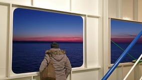 Дама смотря через уничтожает пока ирландский паром выходит Cherbourgh во Францию к гавани Дублина во время захода солнца - сток-видео