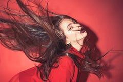Дама с составляет развевать ее волосы Женщина со стильным макияжем и длинными волосами представляя в полном красном обмундировани стоковые изображения rf