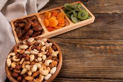 Даты, высушенные абрикосы и кивиы в Compartmental блюде и ассортименте гаек в деревянном шаре на темном деревянном столе стоковые фото
