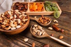 Даты, высушенные абрикосы и кивиы в Compartmental блюде и ассортименте гаек в деревянном шаре на темном деревянном столе скопируй стоковые фото