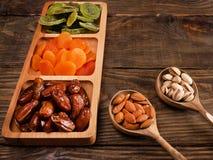 Даты, высушенные абрикосы и кивиы в Compartmental блюде и гайки в деревянной ложке на темном деревянном столе скопируйте космос стоковое фото