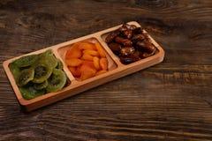 Даты, высушенные абрикосы и кивиы в Compartmental блюде на темном деревянном столе скопируйте космос стоковое изображение rf