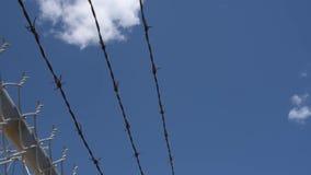 Двигать вдоль верхней части загородки barbwire на голубом небе видеоматериал