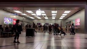 Движение людей играя iphone внутри магазина Яблока