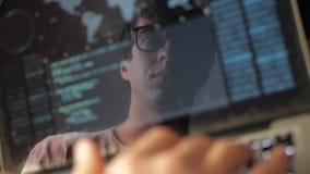 Двойная экспозиция: программист человека в деятельности стекел на ноутбуке Программист пишет голубой код, отражение в мониторе сток-видео