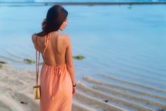 Девушка брюнета взгляда задней стороны с длинными волосами в платье пляжа и плетеная сумка на длинном ремне представляя на пляже стоковое фото rf