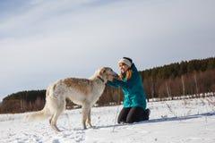 Девушка в зеленой куртке лыжи на ее коленях и русская белая гончая в снежном поле в солнечной зиме стоковые фотографии rf