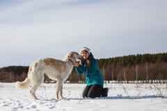 Девушка в зеленой куртке лыжи на ее коленях и русская белая гончая в снежном поле в солнечной зиме стоковое фото rf