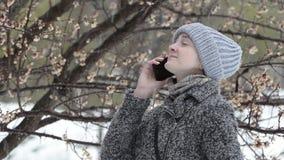 Девушка в шляпе говорит по телефону Весна, sleet сток-видео