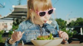 Девушка в розовых стеклах ест салат на спортивной площадке лета кафа Летний отпуск с концепцией детей сток-видео