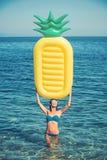 Девушка загорая на пляже с тюфяком воздуха Сексуальная женщина на карибском море в Багамских островах Тюфяк ананаса раздувной стоковое фото