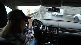 Девушка идет на шоссе Много автомобили на дороге Она следовать навигатором и смотрит вокруг 4K медленный mo сток-видео