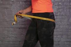 Девушка использует измеряя чашку для того чтобы измерить окружность тела стоковая фотография