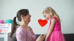 Девушка и ее мама держа бумажные сердце и целовать видеоматериал