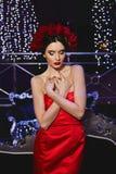 Девушка модного брюнета тонкая модельная с ярким макияжем и с красным флористическим венком на ее голове в красной стильной сатин стоковые изображения