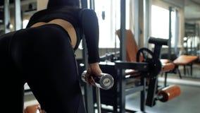 Девушка привлекательных форм в черных гетры делает трицепс тренируя с гантелью на стенде задний взгляд акции видеоматериалы