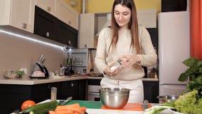 Девушка подготовила салат овоща и соль льет на ем акции видеоматериалы