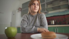 Девушка портрета пухлая думает что она должна съесть вкусный гамбургер или сочное зеленое яблоко Трудный выбор  сток-видео